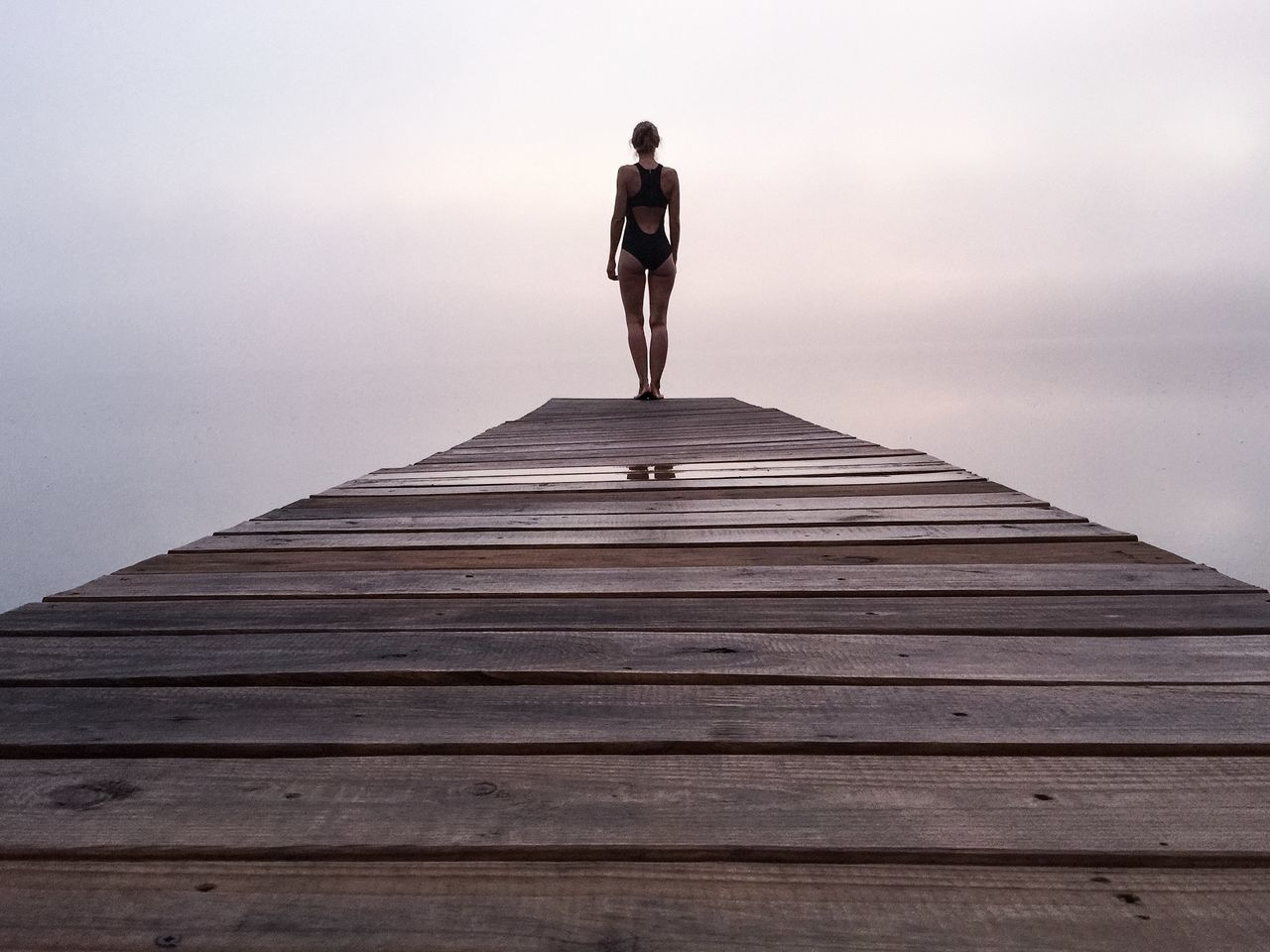 Full length of a woman standing on jetty against clear sky