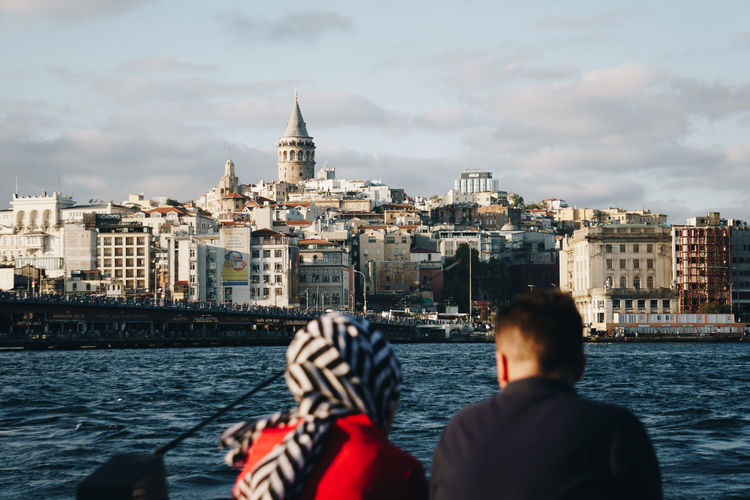 A couple overlooks Istanbul from accross the river. - IG: @LostBoyMemoirs (All photos taken on Sony A6300 and edited in Lightroom). Istanbul Turkey Turkish EyeEm Best Shots The Week on EyeEm Streetwise Photography Streetphotography Street Photography People People Watching people and places Travel River Nature Real People Cityscape Couple Relationship The Art Of Street Photography