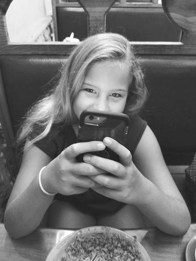 Portrait of girl using mobile phone at restaurant