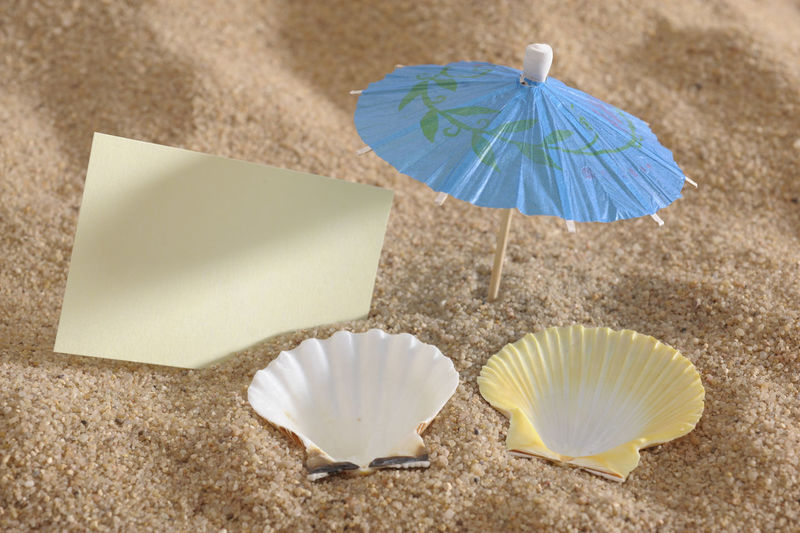 High angle view of seashells and drink umbrella with blank paper on sand