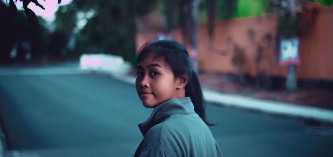 Portrait of teenage girl standing on street in city
