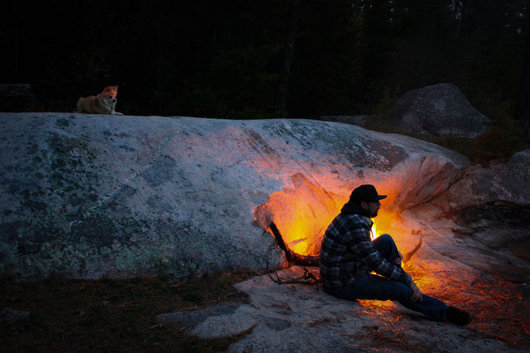 People sitting on rock by water at night