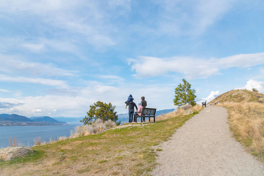 Penticton, British Columbia/Canada - March 21, 2016: a young family enjoys the view of the Okanagan Valley from Munson Mountain, an extinct volcano that is a popular viewpoint for tourists and locals. Afternoon British Columbia, Canada Children Family Kids Lookout Munson Mountain Naramata Naramata Bench Okanagan Lake Scenic Tourists Travel View Blue Sky Editorial  Extinct Volcano Mammal Mountain People South Okanagan Spring Tourism Trail Viewpoint