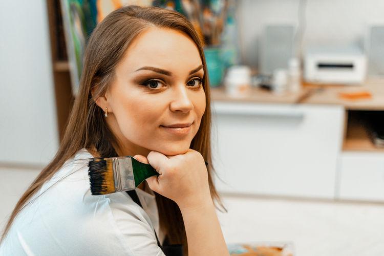 Close-up portrait of smiling woman holding paintbrush