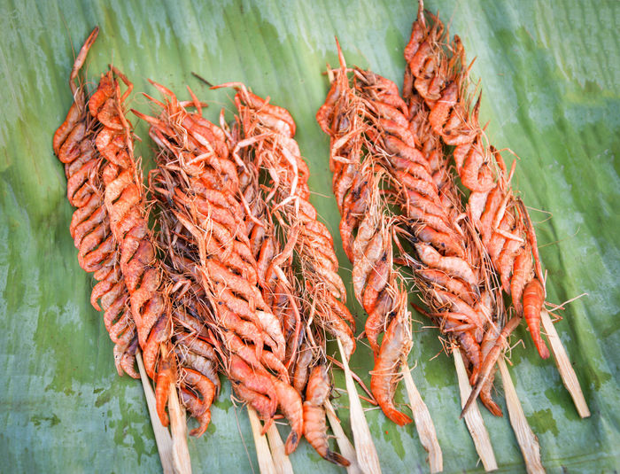 Freshwater small shrimps grilled crispy with stick and seasoning on banana leaf in the street food market ASIA Asian  Background Batter Carrot Closeup Cooked Cooking Crispy Deep Delicious Diet Dinner Dish Fish Flour Food Fresh Freshwater Fried Golden Healthy Homemade Krill Lunch Meal One Onion Orange Pepper Plate Prawn Red Rice Sauce Seafood Shrimp Shrimps Small Snack Street Sweet Thai Thailand Tiny Traditional Vegetables Water White Yellow