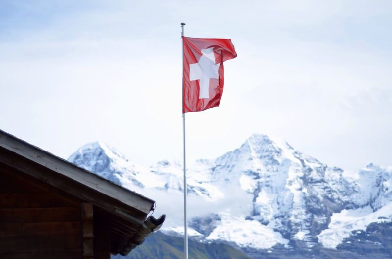 Flag against rocky snow covered mountains