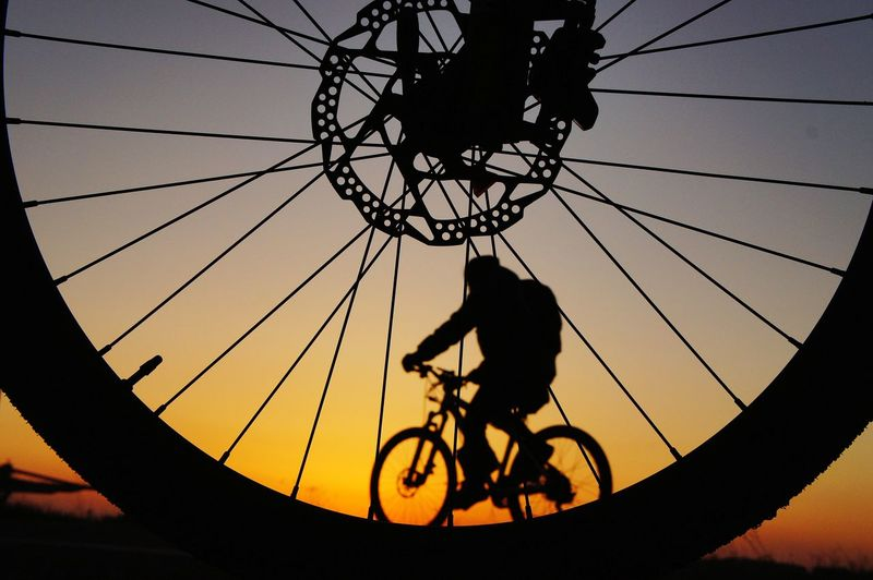 Silhouette Man Riding Bicycle Against Sky Seen Through Spokes