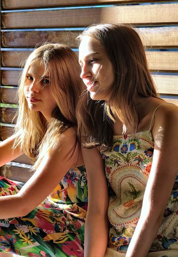 Sisters sitting together against wooden wall