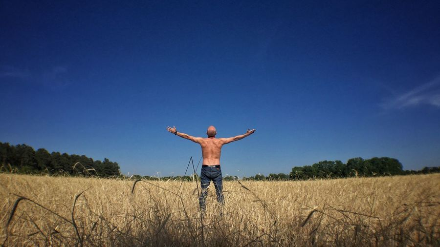 Rear View Of Shirtless Man With Arms Outstretched Standing On Field