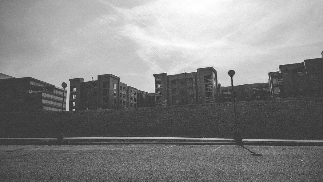 Architecture Black & White Black And White Building Exterior Buildings Buildings & Sky Buildings And Sky Lamp Posts Light & Shadow Light And Shadow Light Posts Overcast Parking Lot Sidewalk Sky Streaks Street Lights Sunlight