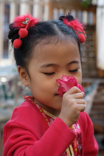 Close-up portrait of cute girl holding red flowers