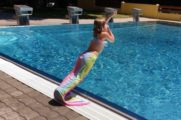 Full length of girl diving in swimming pool