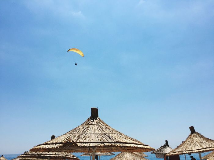 Low angle view of parachute flying over parasols against sky
