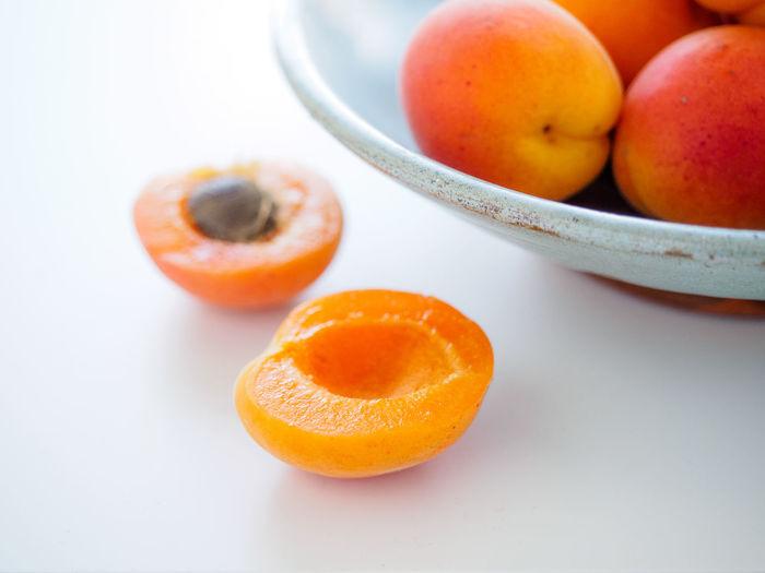 Close-up of orange fruit over white background