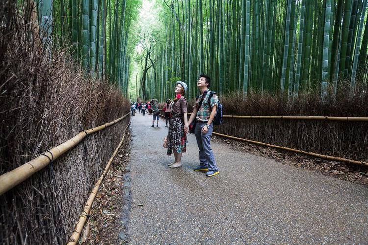 Smiling couple standing on pathway amidst bamboos at arashiyama
