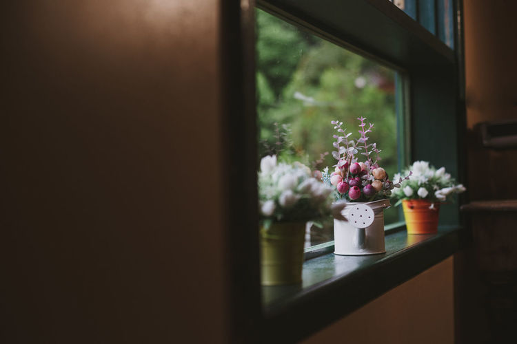 Artificial flower pots on window sill at home