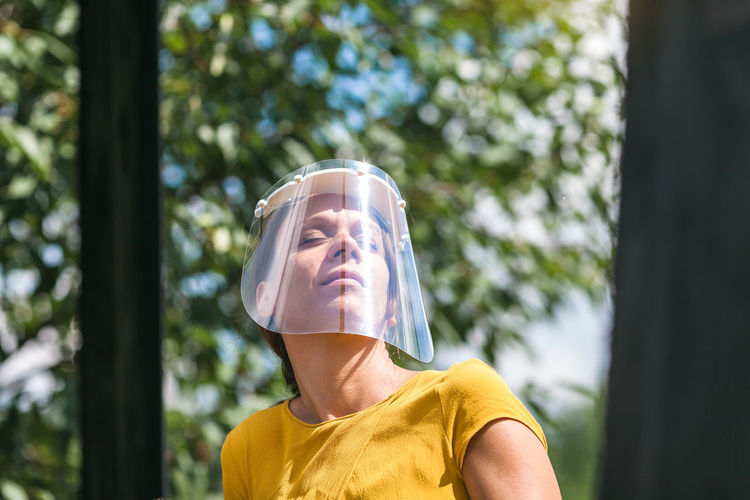 Close-up of woman wearing face shield against trees