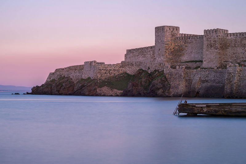 Castle by sea against sky during sunset