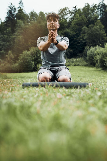 Young man doing exercises outside on grass during his calisthenics workout