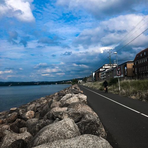 Sky Cloud - Sky Road Transportation Water Nature The Way Forward Diminishing Perspective Beauty In Nature Direction Incidental People Scenics - Nature Outdoors Sea Built Structure Day Architecture Tranquil Scene Building Exterior