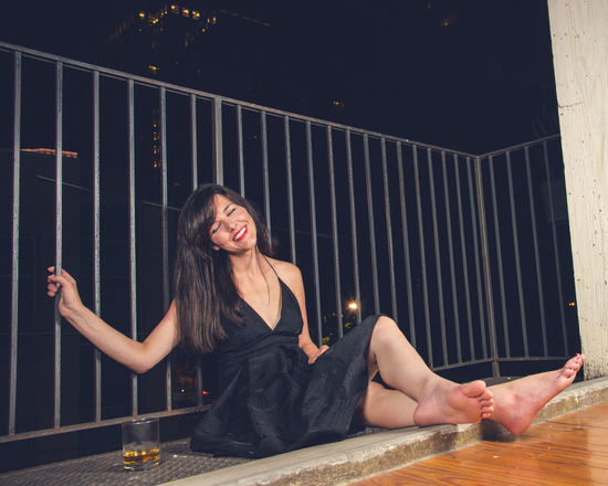 Enjoying the city sounds About Last Night Bare Feet Beautiful Woman Brunnette City Life Fence Iron Iron Rails Little Black Dress Night Outside Pretty Woman Red Lips Smiling Whiskey
