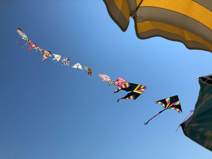 Low angle view of colorful kites flying against clear blue sky