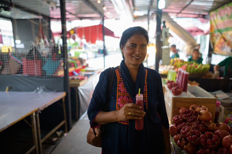 Portrait of smiling woman standing at market