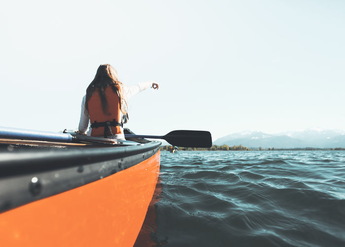 Rear View Of Woman Kayaking In Chiemsee Lake