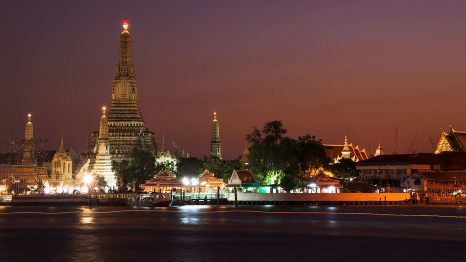 Wat Arun at dusk near Chao Phraya river, Bangkok Arun Bangkok Pagoda Travel Architecture Belief Building Building Exterior Built Structure City Illuminated Nature Night No People Place Of Worship Religion Sky Skyscraper Spirituality Sunset Travel Travel Destinations Wat Water