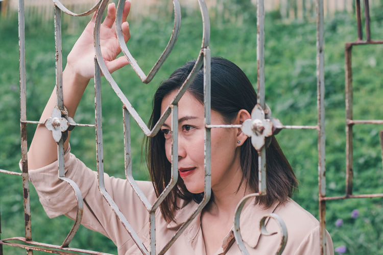 Portrait of young woman holding umbrella by fence
