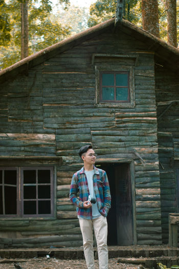 Man standing against old house