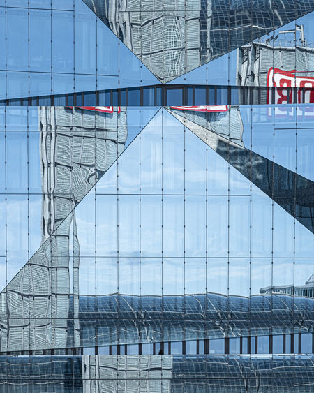 Reflection of bridge on building in city