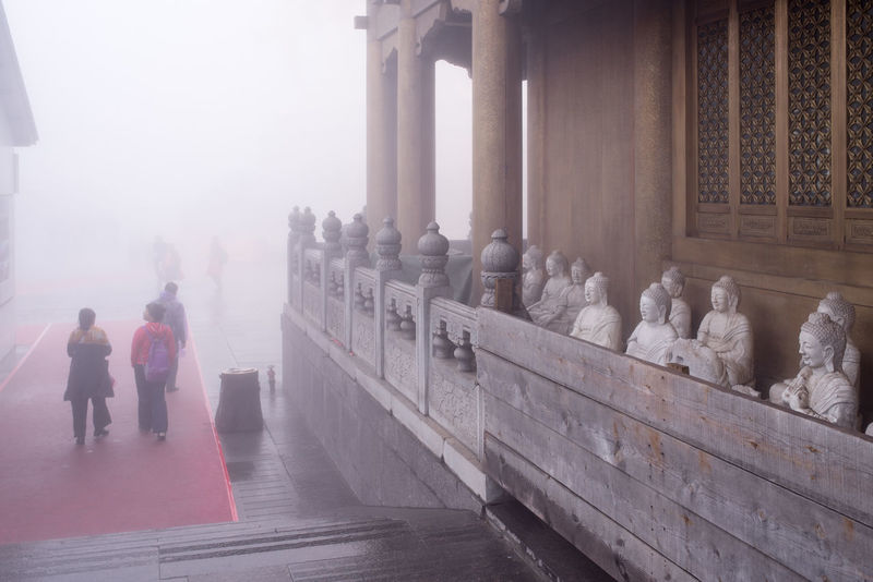 A statue of smiling Buddha with part of the face covered by rain cloth. Atmosphere Buddha Sitting Tourists Fog Mysterious Pass By People Smiling Statue Temple Visitors Watching