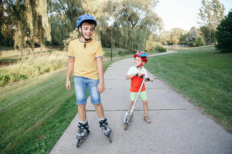 Full length of boys on footpath in park
