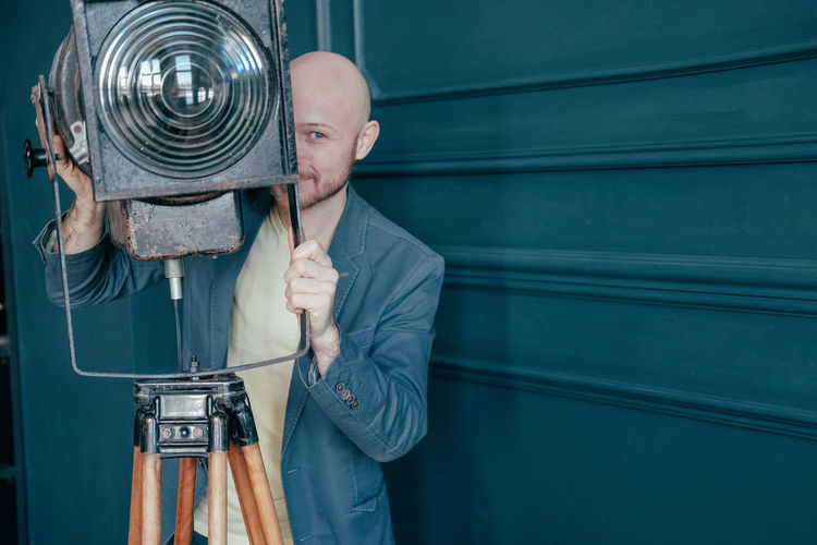 Man holding camera while standing against blue wall