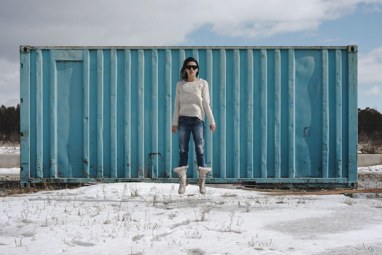 Full length of woman levitating against metallic container during winter