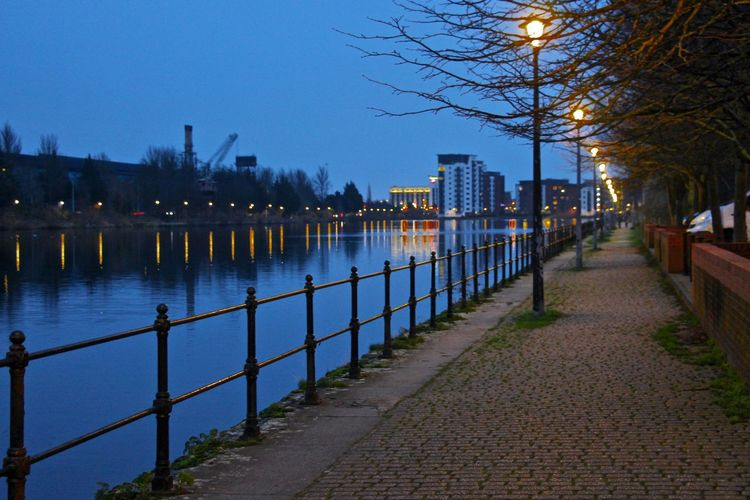 Footpath by river in city against sky at dusk