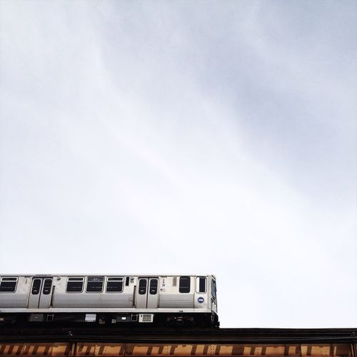 Low angle view of cropped train against sky
