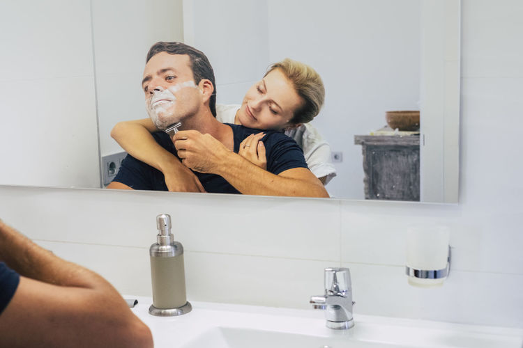 Man shaving beards while woman embracing at bathroom