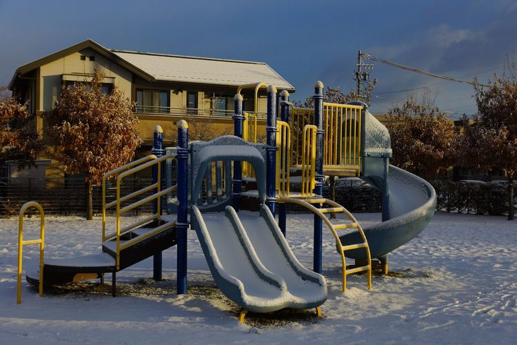 Snow covered slide on playing field at park