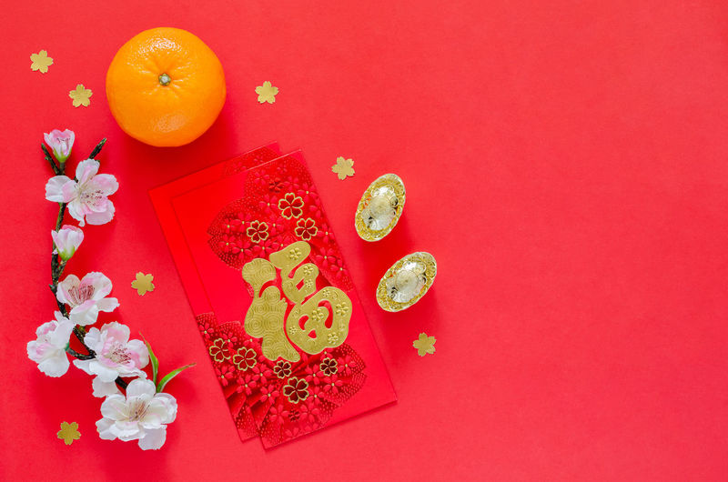 High angle view of orange paper against colored background
