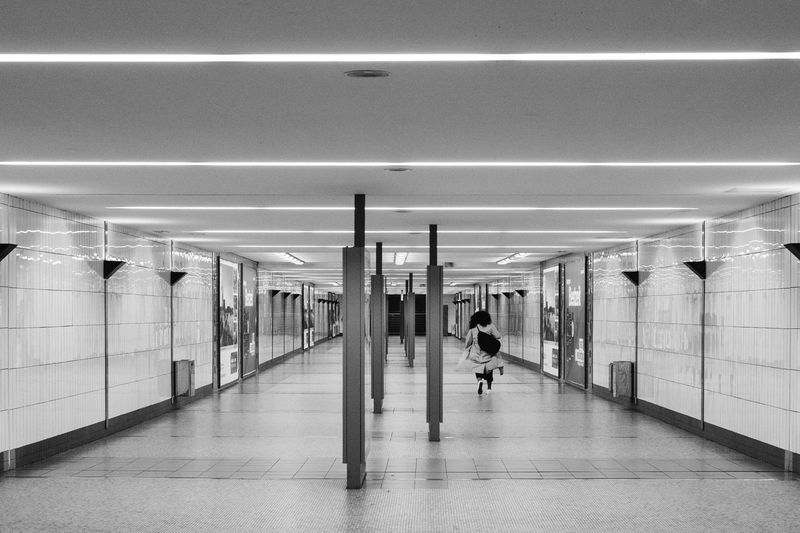Architectural Column Blackandwhite Casual Clothing City Life Column Corridor Flooring Full Length Illuminated Leisure Activity Lifestyles Modern Monochrome The Way Forward Tile Underground