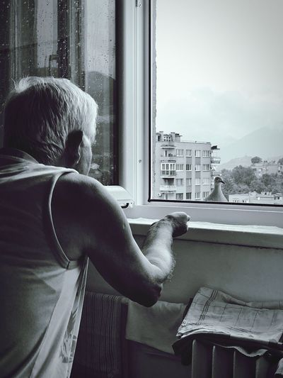 Rear view of senior man looking through window at home
