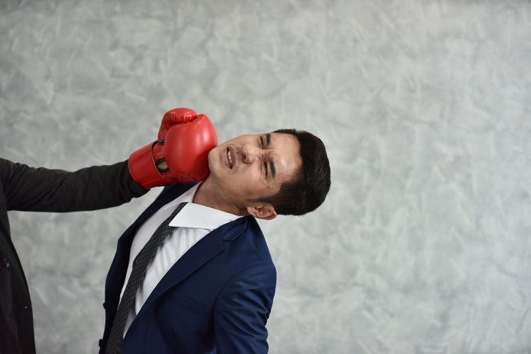 Businessman ready to fight with boxing gloves over gray background. Business man ready to fight with boxing gloves. Young businessman with boxing gloves One Person Front View Men Sport Real People Boxing Glove Adult Lifestyles Wall - Building Feature Males  Business Waist Up Business Person Indoors  Red Leisure Activity Standing Businessman Mature Men Punching