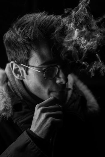 Close-up of young man smoking cigarette in dark