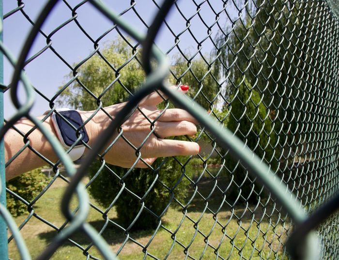 Man seen through chainlink fence