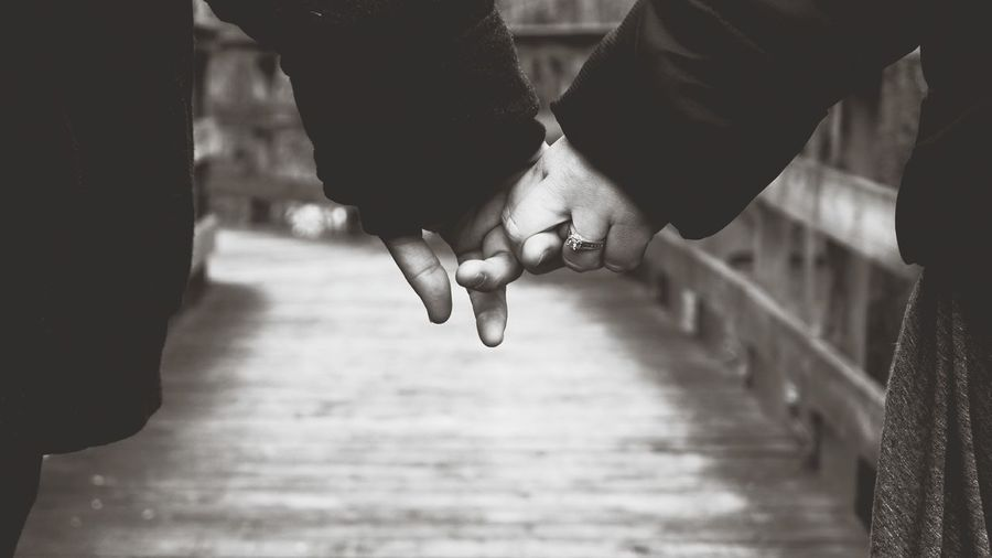 Close-up of man and woman holding hands on boardwalk