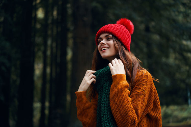 Young woman looking away in forest during winter