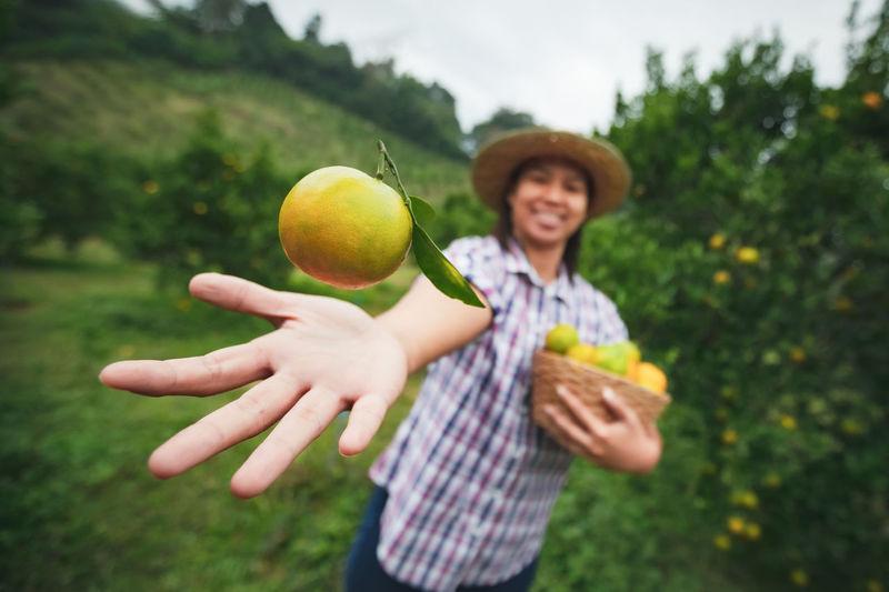 Woman throwing orange while standing at farm