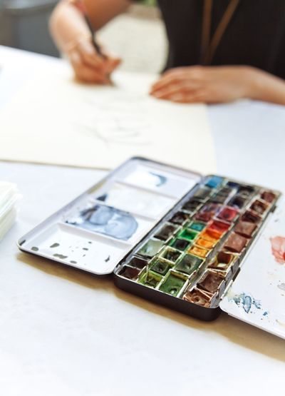Midsection of woman sketching with colorful paints in foreground at table